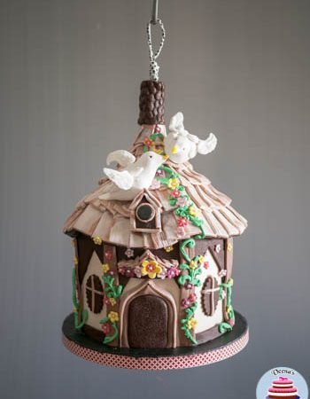 A cake decorated to look like a hanging birdhouse.
