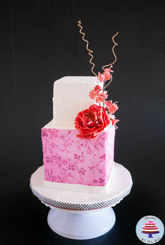 A wedding cake decorated in a cherry blossom theme.