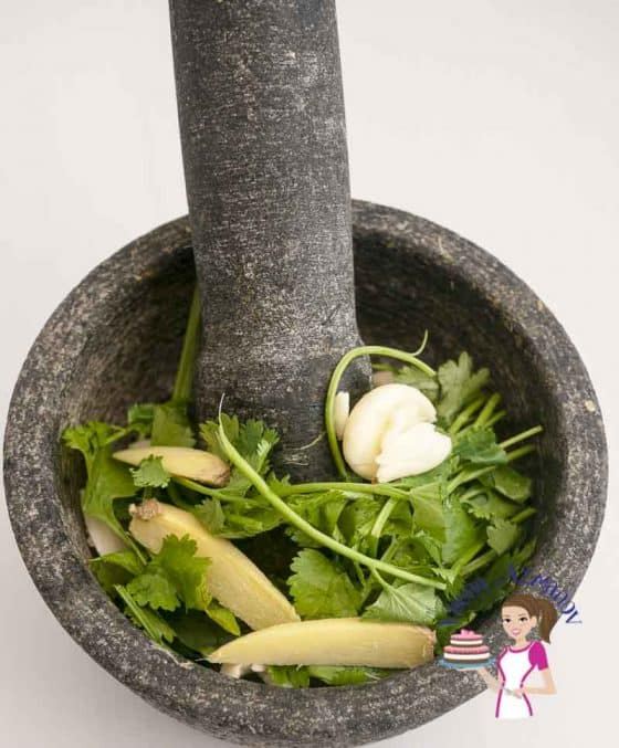 Grinding cilantro, ginger and garlic with a mortar and pestle.