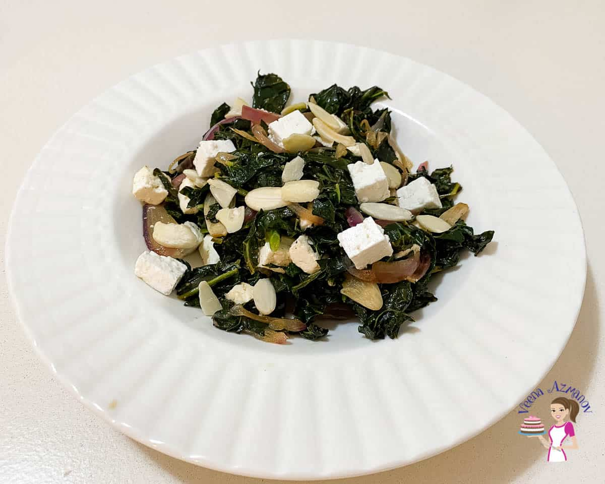 A plate with kale, olives, and feta