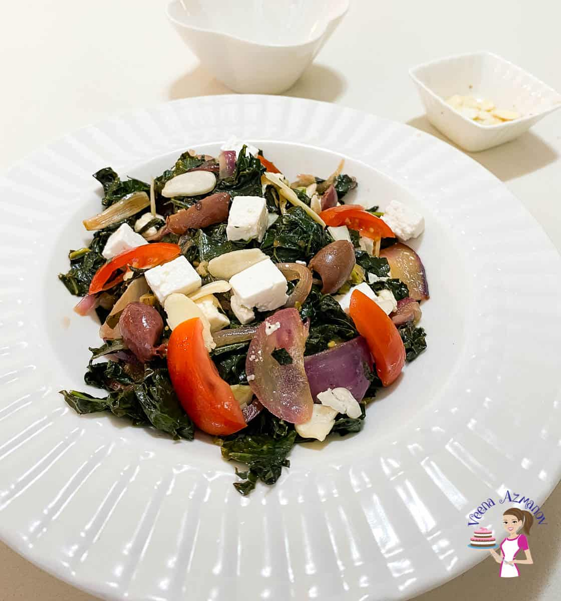 A white plate with kale, feta and olives