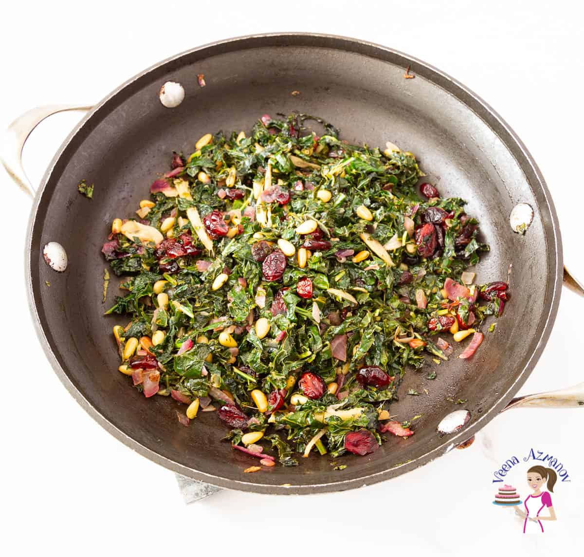 A skillet with kale sauteed with pine nuts