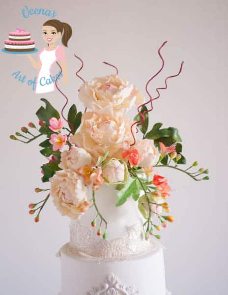 A white wedding cake with sugar peony flowers on top.