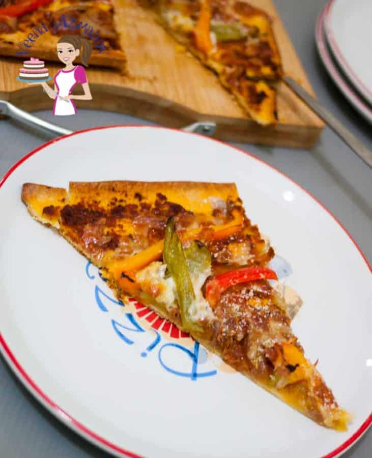 A slice of red pesto pizza with bell peppers.
