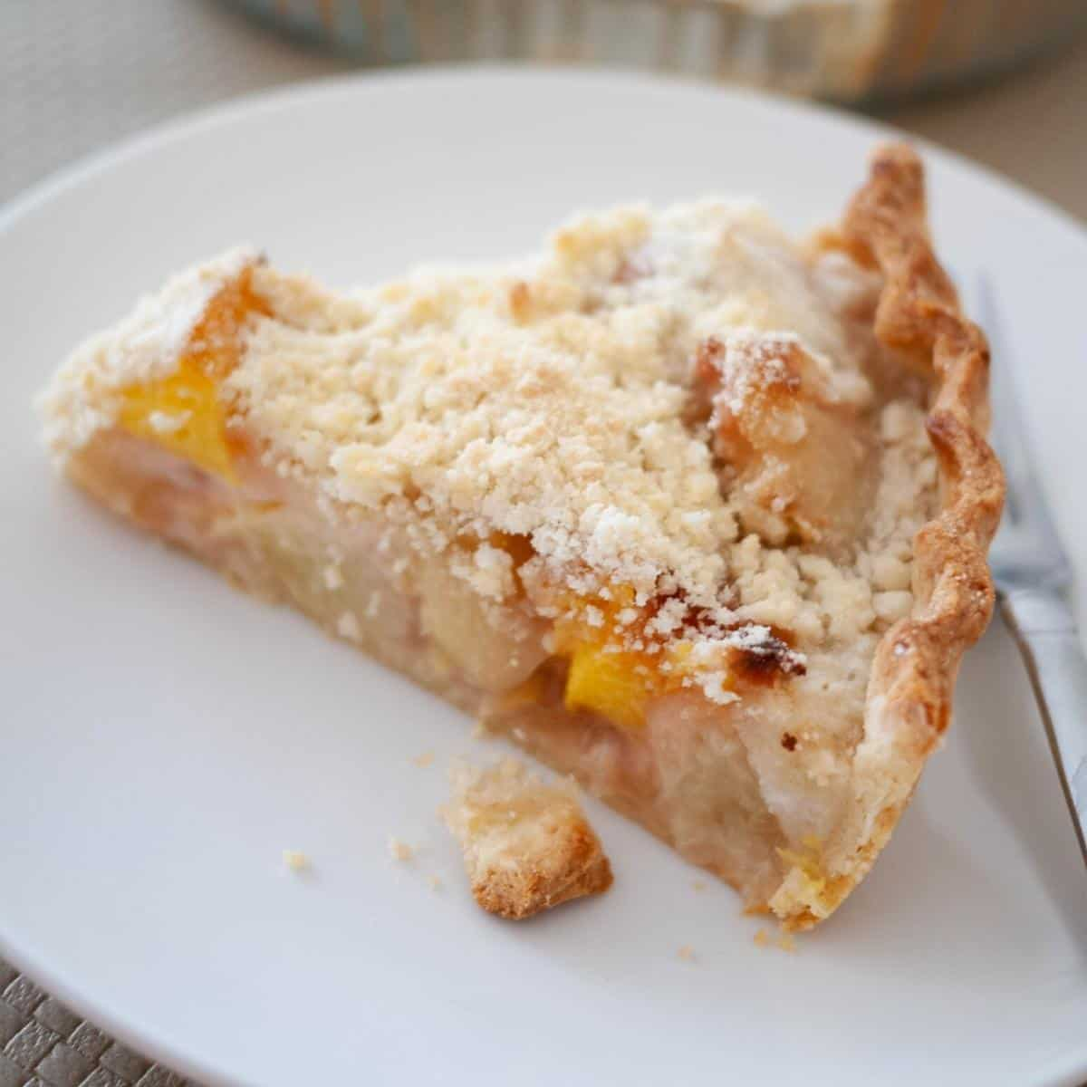 A slice of peach pie with crumble top.