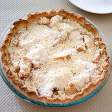 A pie with peaches on a table.