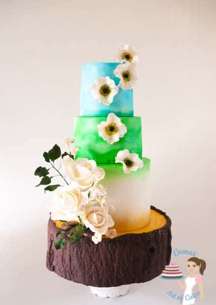 A summery Tree Stump inspired wedding that showcases the blue clouds and green pastures, the white of purity; all perched on a tree stump cake. A unique but gorgeous creation by Veena Azmanov of Veena's Art of Cakes