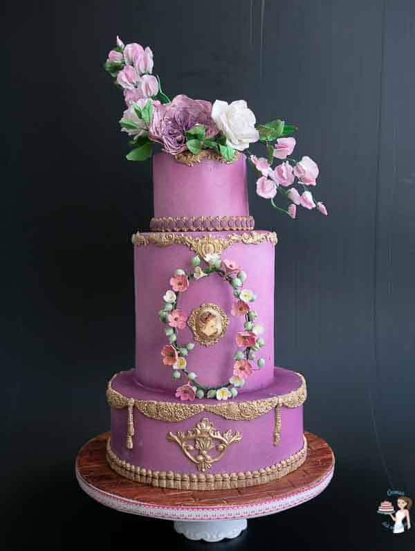 A 3-tier purple cake for the Queen with pink sugar flowers.
