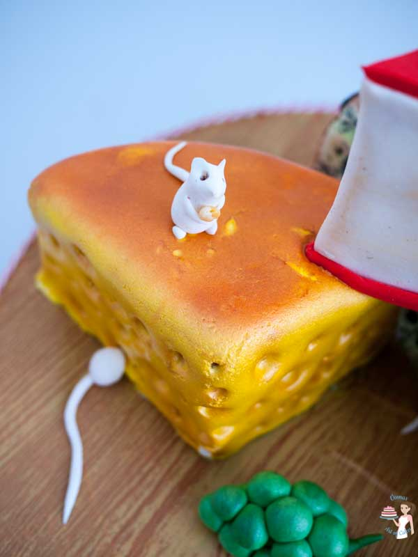 A close up of a cake decorated to look like three pieces of different cheeses.