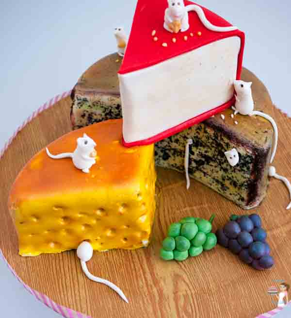 A cake decorated to look like three pieces of different cheese.