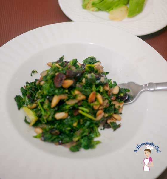 Sauteed Kale in ginger with pine nuts and cranberries is a very simple easy and perfect side dish; very high in nutrition and low in calories which makes it a perfect diet meal by food blog A Homemade Chef.