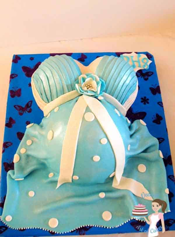 A cake decorated to look like a pregnant belly.