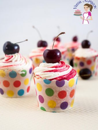 A cupcake made from scratch with cherry puree and almond extract topped with fresh cherry