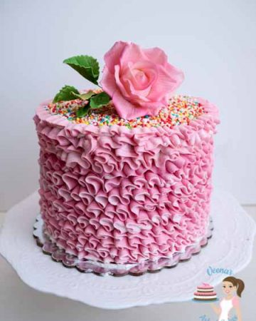 A pink buttercream ruffles cake with a sugar flower on top.