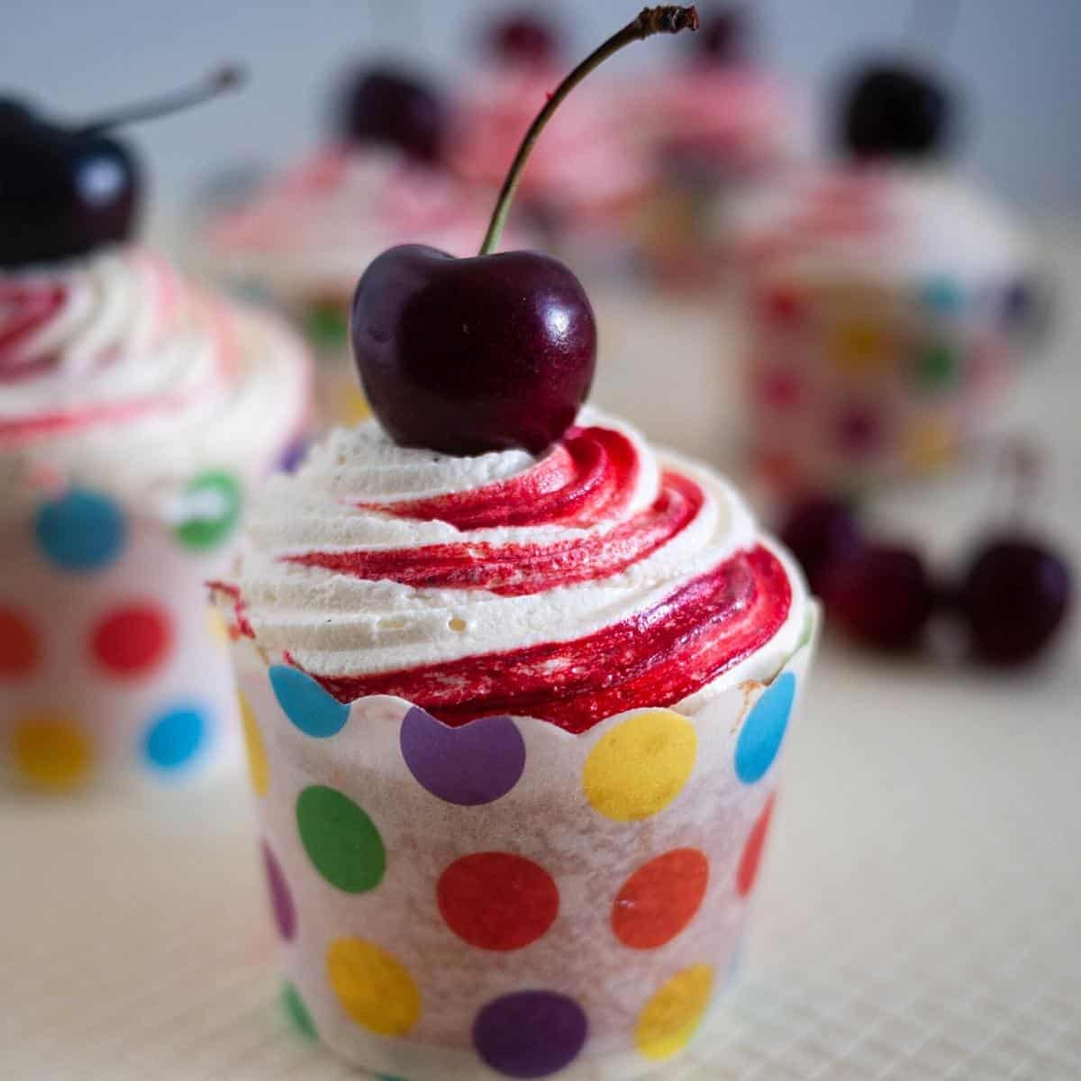 A frosted cupcake with fresh cherry.