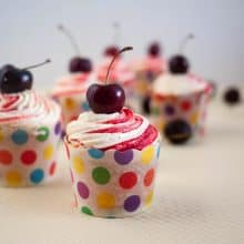 Baking cups with cherry cupcakes.