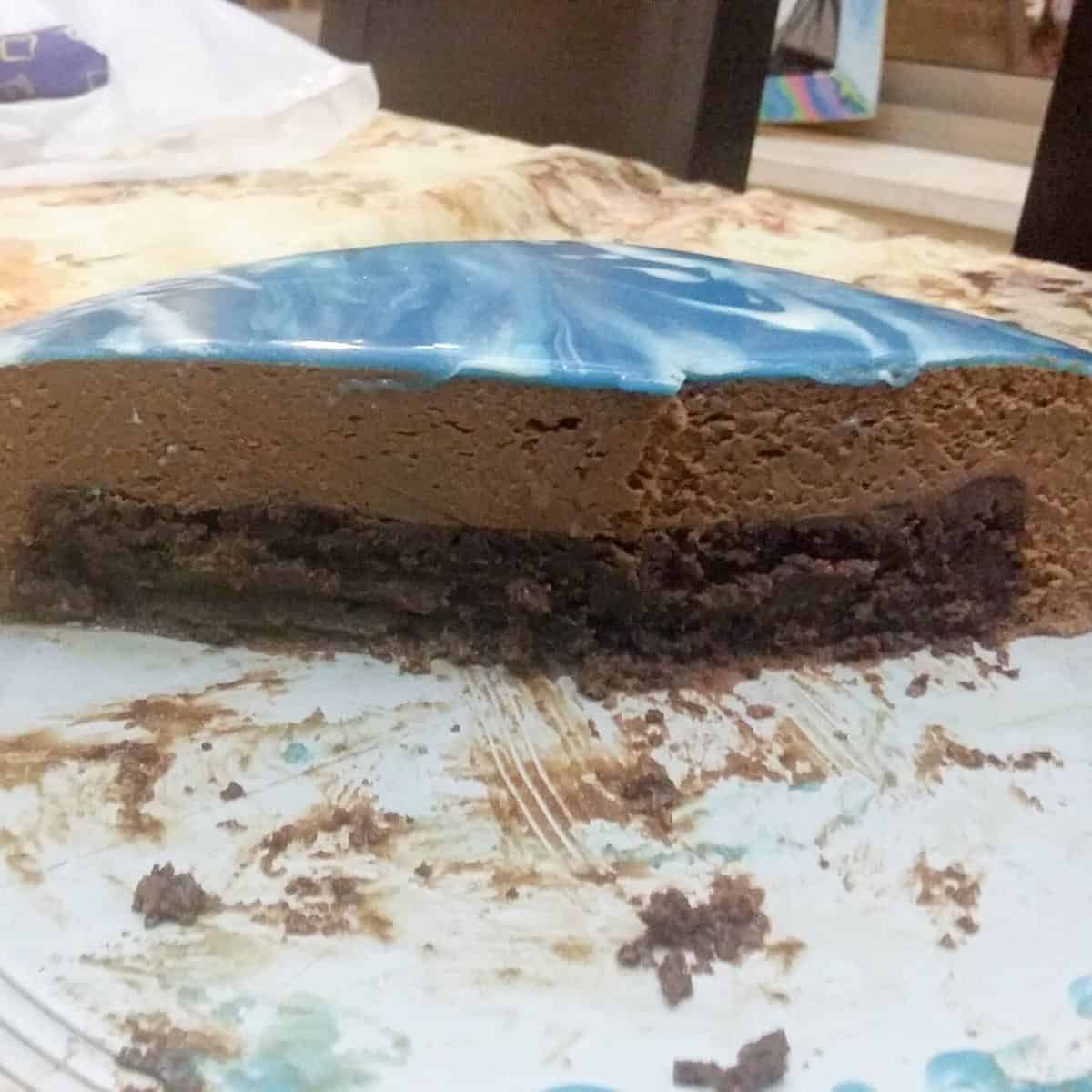 Mousse cake with mirror glaze on cake board.