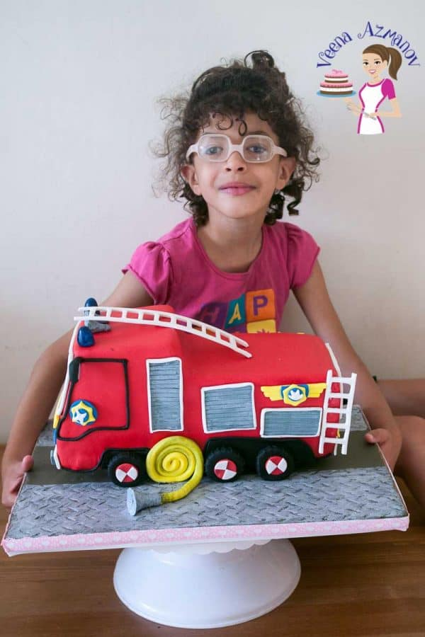 A little girl sitting on a table with her fire truck cake.