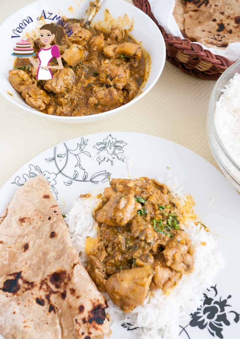 A table served with Indian food. This Quick Chicken Curry with few ingredients - with a basket of Chapati and a bowl of steamed white rice.