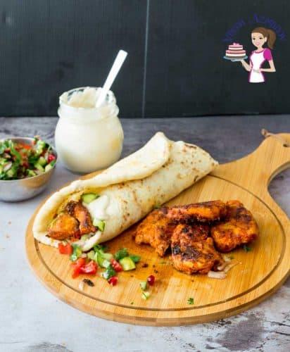 Chicken shawarma wrap on a wooden board.