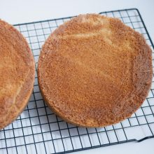 Vanilla cake on a cooling rack.