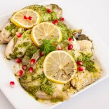 A serving platter with baked fish in cilantro marinade.