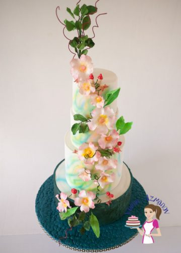 An Enchanted Spring Inspired Wedding Cake inspired by the flowers of spring with mushrooms, blossoms and foliage with a stone embossed bottom tier in navy