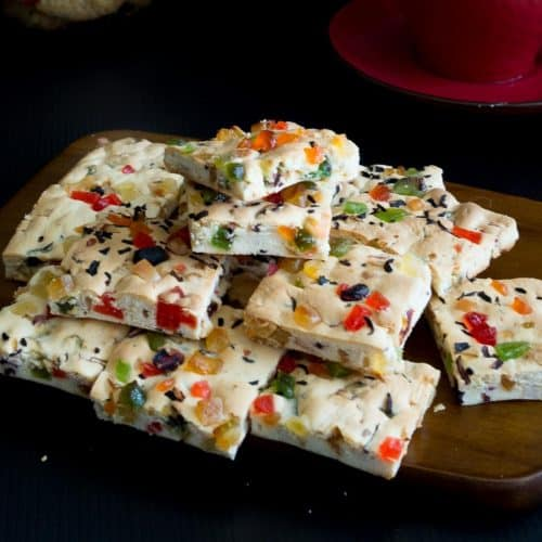 A stack of candied fruit shortbread squares on a board.
