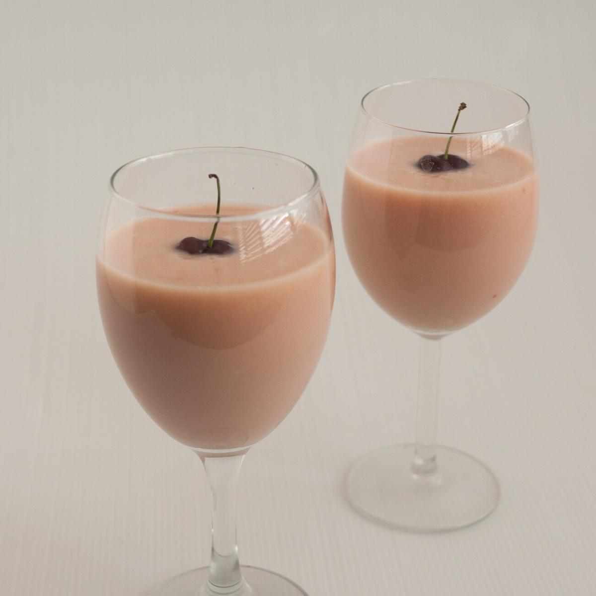 Two wine glasses with cherry eggnog