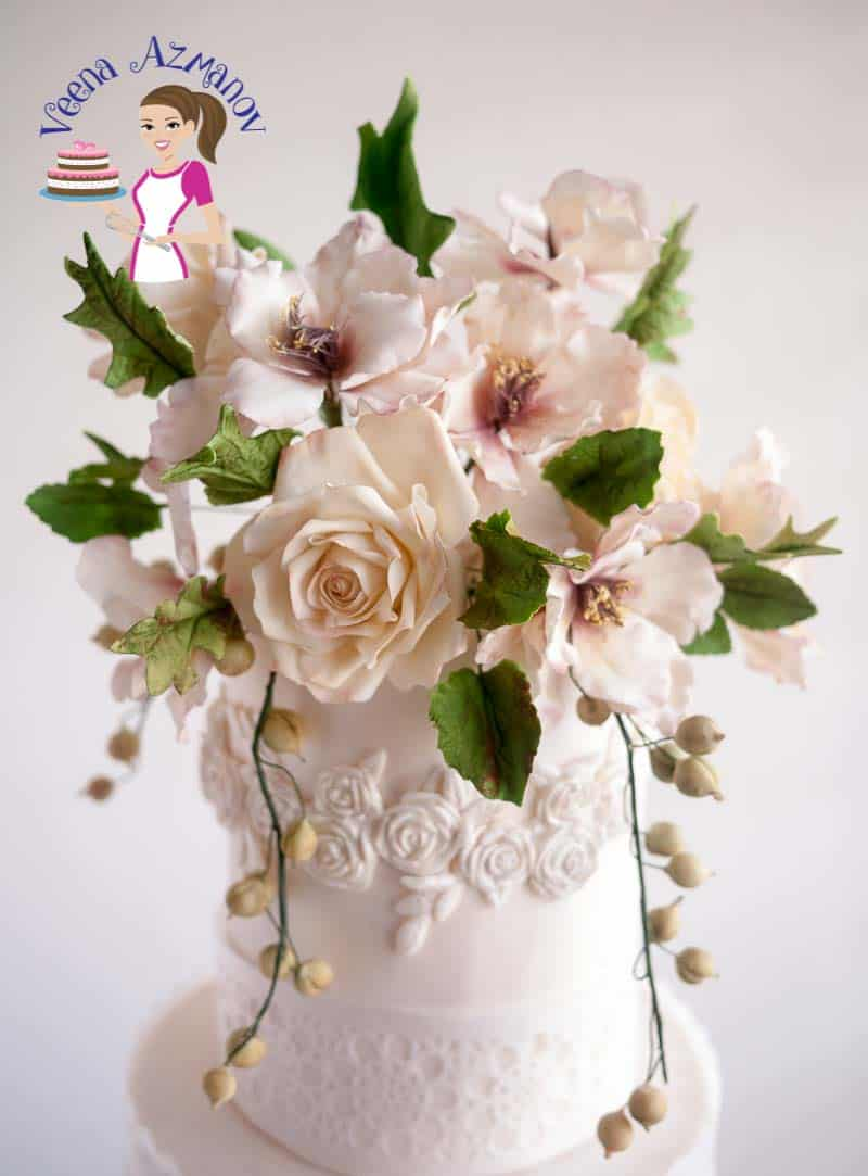 White sugar flowers on top of a wedding cake.