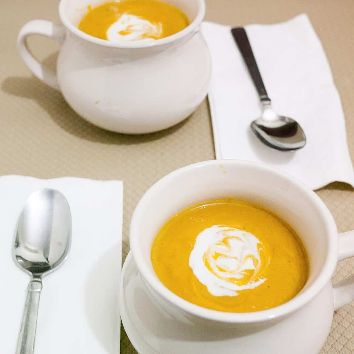 Two bowls with pumpkin soup.