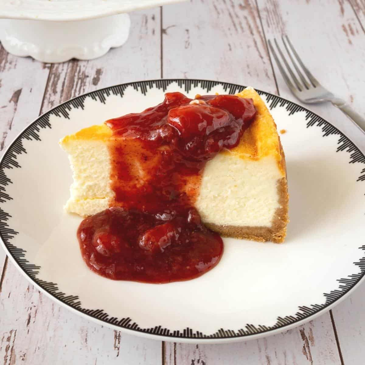 A slice of strawberry cheesecake on a plate.