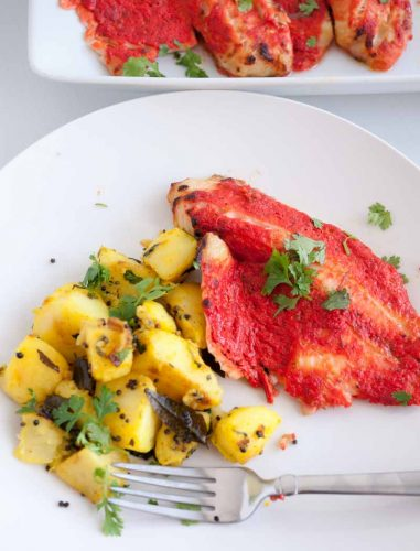A plate with tandoori fish and baked potatoes.