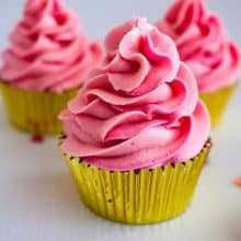 A pink Champagne buttercream frosted cupcake in a golden cupcake liner.
