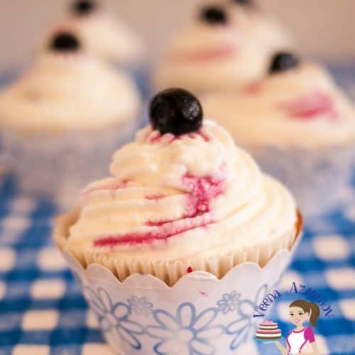 A blueberry cupcake with cream cheese frosting.