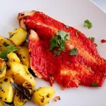 A white plate with tandoori fish.