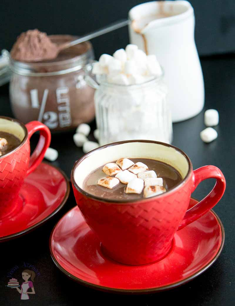 A classic shot of this Hot Chocolate Recipe - the drink is featured with melted marshmallows with hot cocoa mix in the background