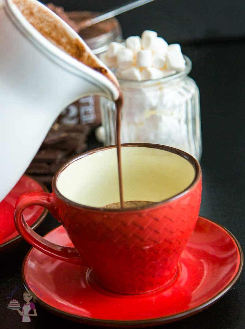 A pouring shot of an almost full Homemade Hot chocolate Recipe - featuring the hot chocolate drink is thick and creamy