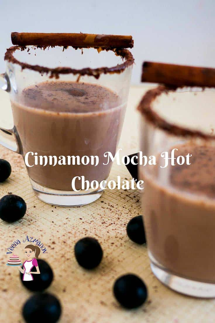 Two cups of Cinnamon Mocha Hot Chocolate in a glass cups, garnished with a cinnamon stick and grated chocolate