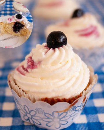 A frosted lemon cupcake with blueberry filling and cream cheese frosting.
