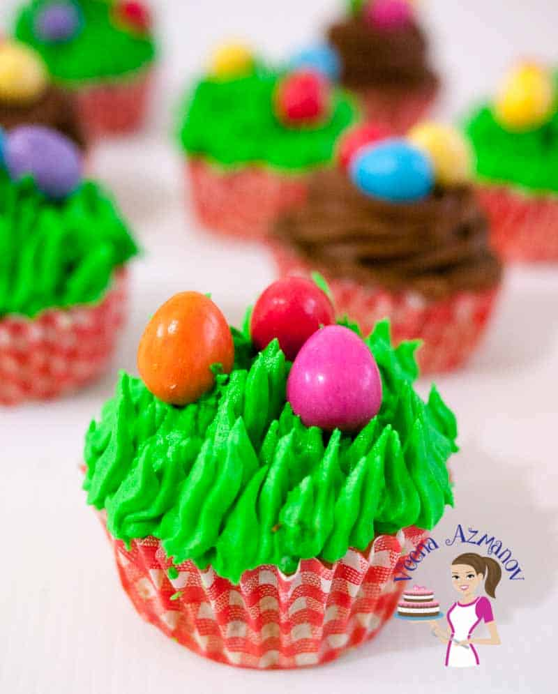 A Close up of this Festive Carrot Cupcakes with Easter Eggs - this one is piped green grass with candy easter eggs
