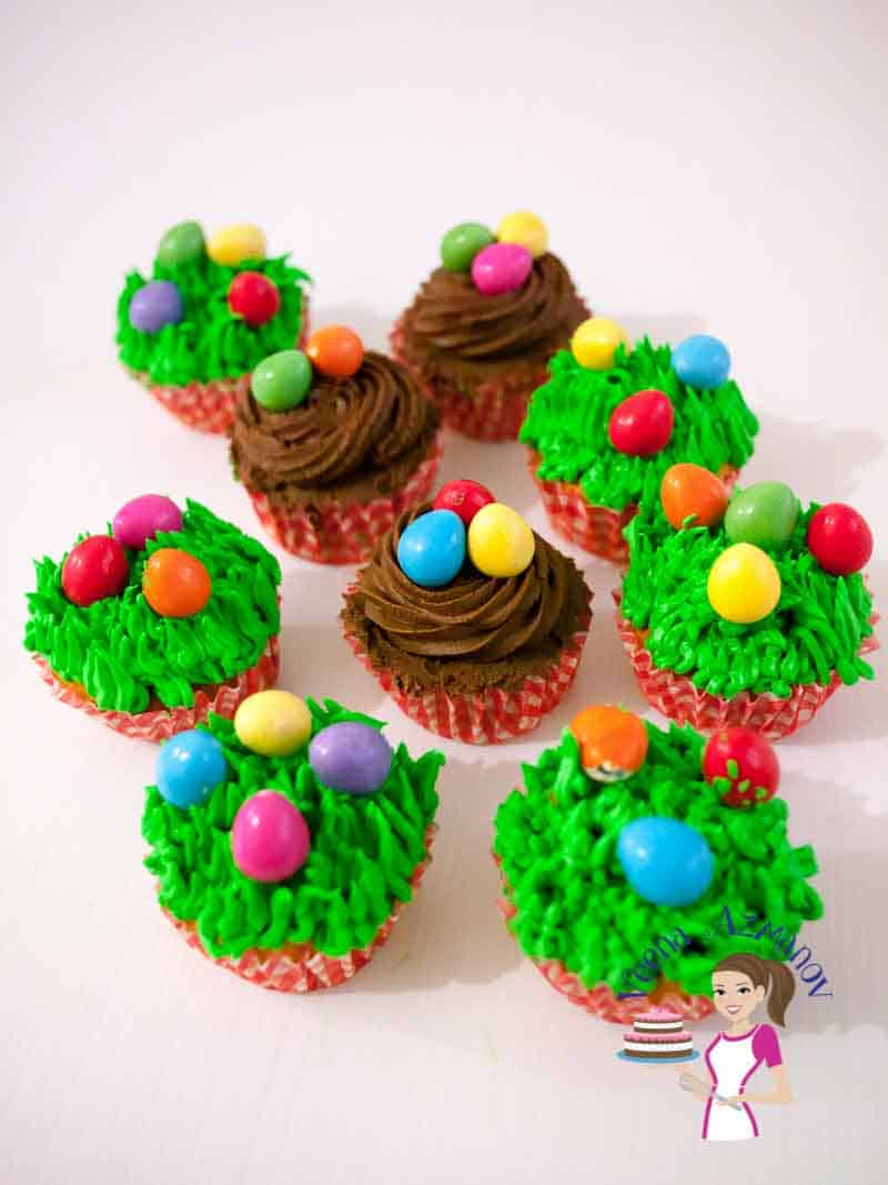 A Collection of festive carrot cupcakes with adorned with easter eggs and brown nest and grass