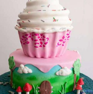 A birthday cake designed like a big cupcake with white frosting.