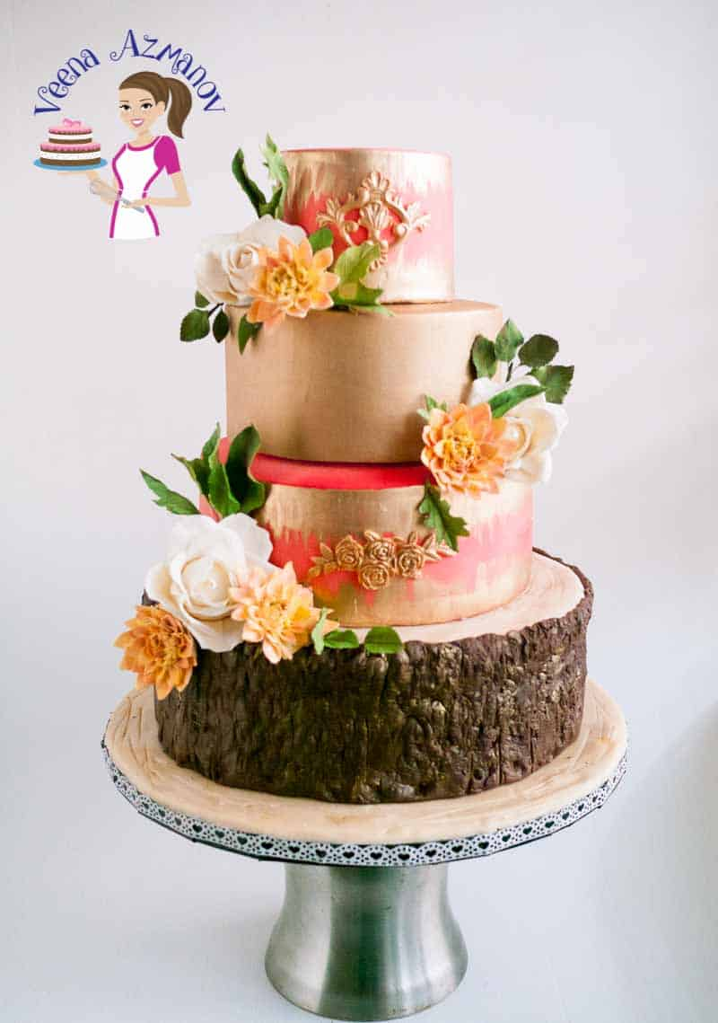 This Dahlia Gold wedding cake is four tiers of deliciously flavored cake from creamy coconut, chocolate fudge to Zesty lemon and moist carrot goodness. Covered to perfection and adorned with sugar Dahlia, roses and foliage.