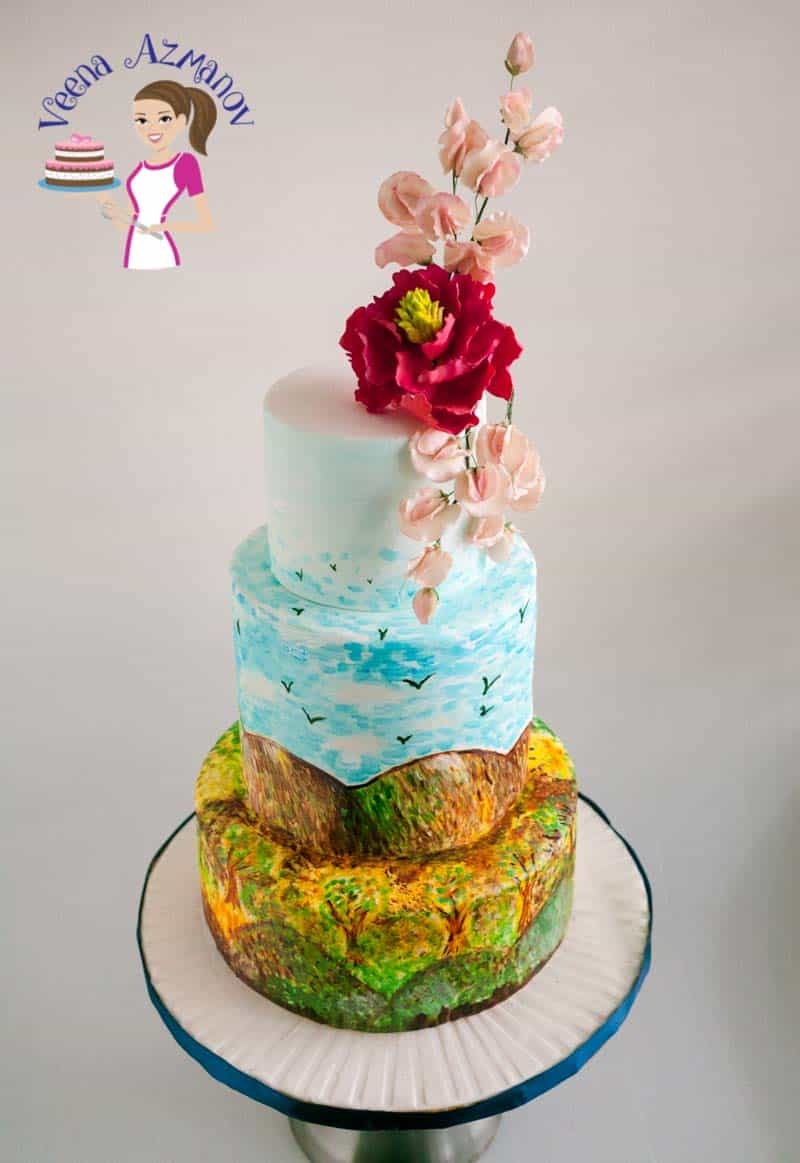 A hand painted cake with sugar flower on top.