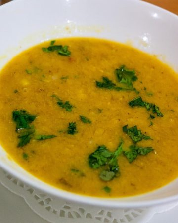A white bowl with yellow lentils