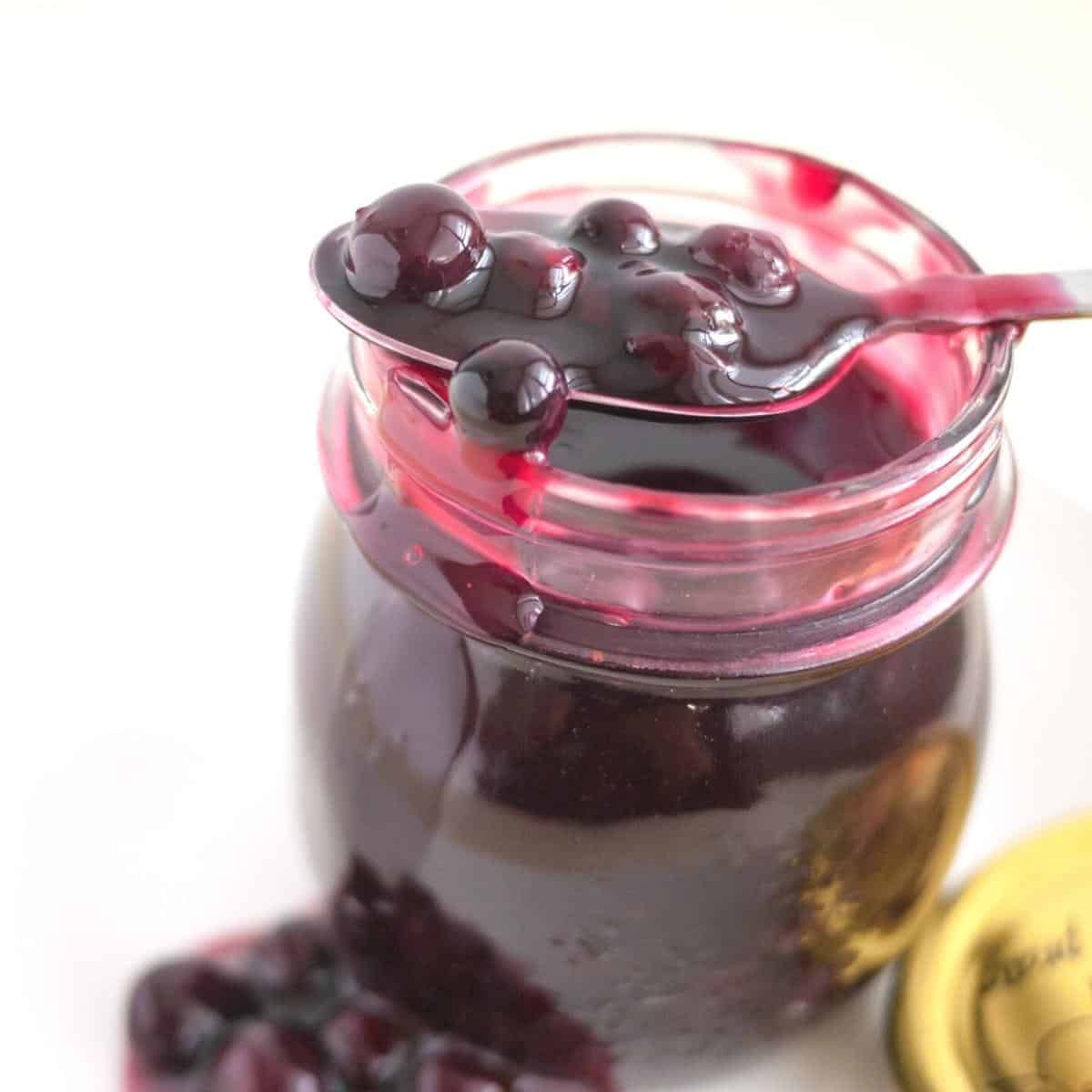A mason jar with blueberry fruit filling.