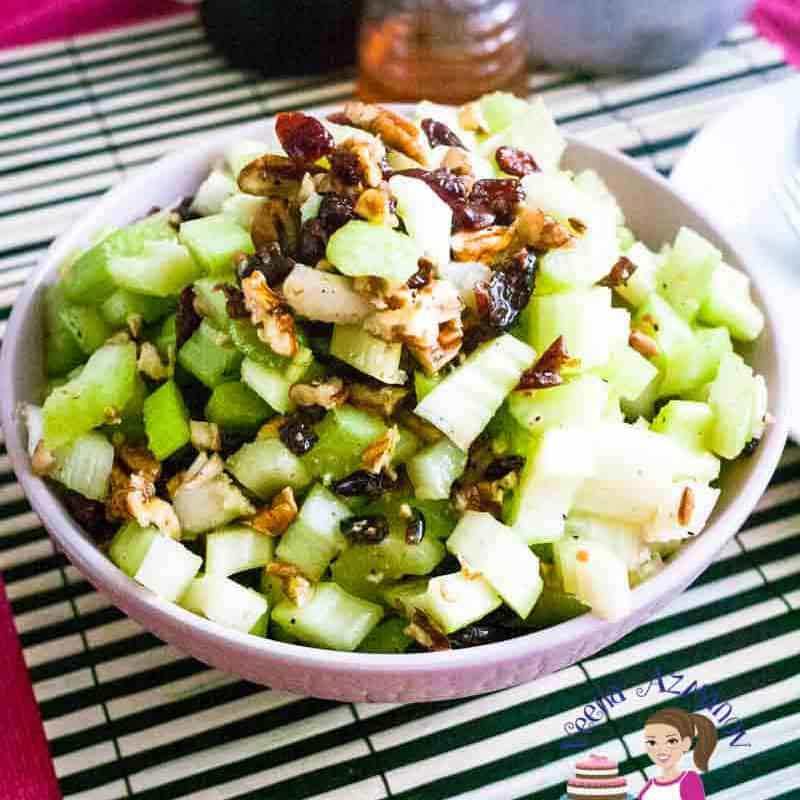 A bowl of celery salad with pecans and cranberries.
