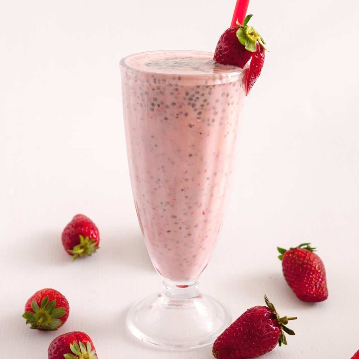 A tall glass of smoothie and strawberries
