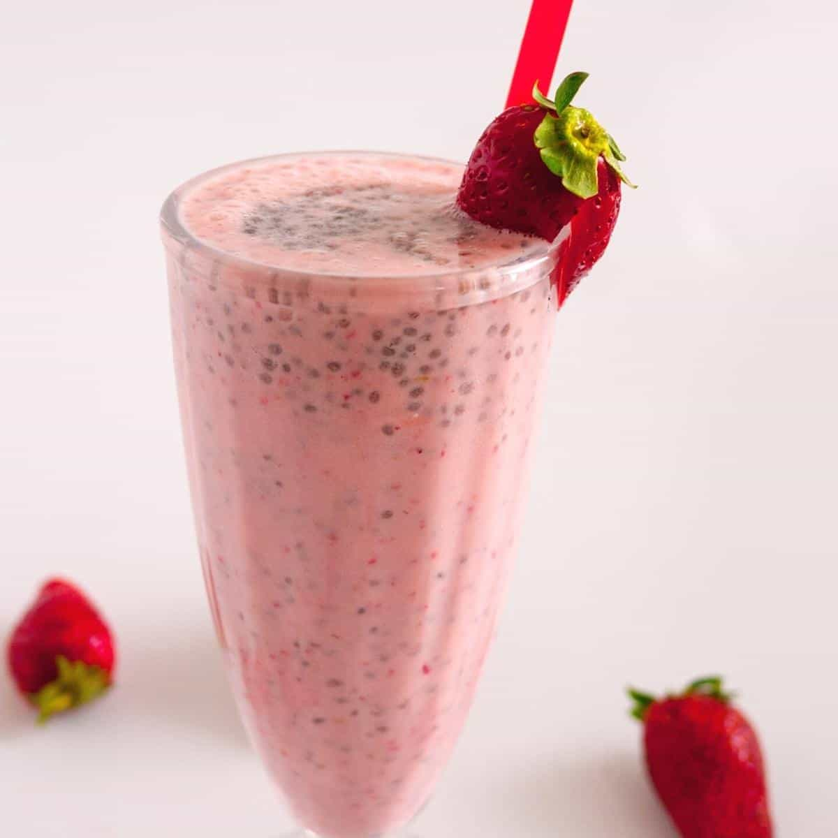 A milkshake glass with strawberries and banana